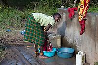 Tanzania.  Maasai Woman Doing her Laundry, Ololosokwan Village, Northern Serengeti.