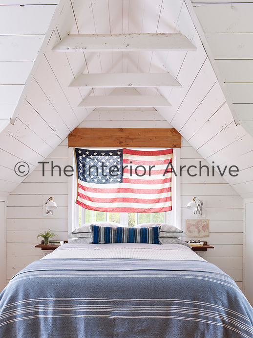 The upstairs loft houses the white, wood panelled master bedroom. The room is light and airy with its vaulted ceiling and the simple blue and white theme gives the space a cool feel. The double bed has wall-mounted bedside shelves and reading lamps.