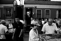 People step out of a long-distance train to buy newspapers and food from vendors in Baoji, Shaanxi, China.