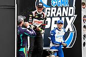 #21: Rinus VeeKay, Ed Carpenter Racing Chevrolet sprays sparkling juice on #51: Romain Grosjean, Dale Coyne Racing with RWR Honda as #10: Alex Palou, Chip Ganassi Racing Honda looks on in the background.