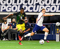 DALLAS, TX - JULY 25: James Sands #16 of the United States and Cory Burke #9 of Jamaica chase after a loose ball during a game between Jamaica and USMNT at AT&T Stadium on July 25, 2021 in Dallas, Texas.
