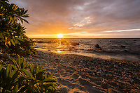 The sun breaks under the clouds and shines its golden light on Puako Bay, Big Island of Hawai'i.