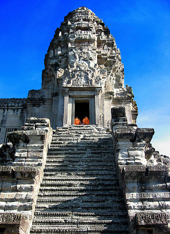 Two Buddhist monks sit in a doorway on top of a temple in Angkor Wat, Siem Reap, Cambodia