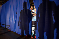 Anna Wrecks Ya (left) and Maura Buse peak through the curtain as their opponents are introduced at the start of a roller derby bout in Wilmington, Massachusetts. Roller derby is an American contact sport, popular with young women, which combines both athleticism and a satirical punk third-wave feminism aesthetic.