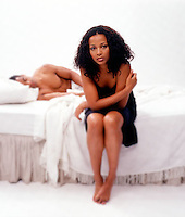 African American woman on edge of bed with man in background<br />