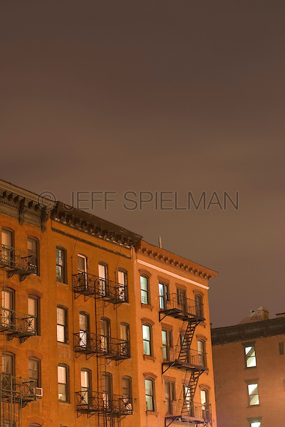 AVAILABLE FROM JEFF AS A FINE ART PRINT.<br /> <br /> AVAILABLE FOR COMMERCIAL AND EDITORIAL LICENSING FROM GETTY IMAGES.  Please search for image # 200566126-001 on www.gettyimages.com.<br /> <br /> Row of 19th Century Tenement Apartment Buildings on Second Avenue Illuminated at Night, East Village, Lower Manhattan, New York City, New York State, USA