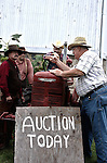 A farm auction today conducted by a auctioner by a barn
