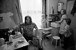 Working class family at home Fulham London 1972. This is their kitchen. They did not have their own bathroom which was shared with other families in the house. The boy is having a face wash.