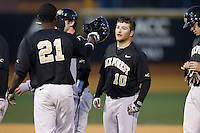 Nate Mondou (10) of the Wake Forest Demon Deacons gets his batting helmet back from Kevin Jordan (21) after the celebration of his walk-off single in the bottom of the ninth inning against the Missouri Tigers at Wake Forest Baseball Park on February 22, 2014 in Winston-Salem, North Carolina.  The Demon Deacons defeated the Tigers 1-0.  (Brian Westerholt/Four Seam Images)