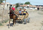 Two men drive a horse-drawn cart through a largely Roma, Turkish-speaking neighborhood of Dobrich, in the northeast of Bulgaria.