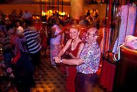 Woman in red dress and partner, swing dancing a nightclub in the Ala Moana Hotel, Waikiki, Oahu, Hawaii