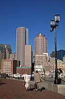 People walk on Federal Courthouse waterfront park promenade with Boston Harbor and city skyline view beyond, Boston, M