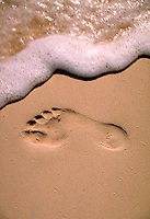 footprint in the sand with sea foam.