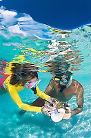 Couple with conch shell snorkeling at Buck Island<br /> St. Croix<br /> U.S. Virgin Islands