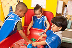 Education Preschool 3-4 year olds three children, two boys and a girl, wearing smocks, playing separately at water table
