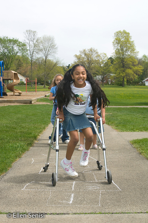 MR / Schenectady, NY.Zoller school (urban public school) / grade 2 Inclusion class.Girl (7, cerebral palsy, in walker) plays game of hopscotch with her friends on the playground..MR: AG-gss, Cha9.© Ellen B. Senisi