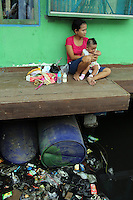 A mother and her child sit next to a severely polluted water channel in a slum community in central Jakarta.