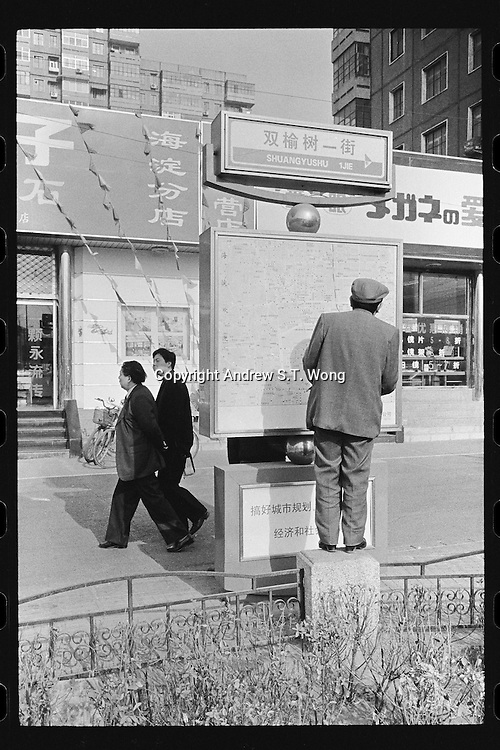 A Chinese man reads a map in Beijing, China, 1999.