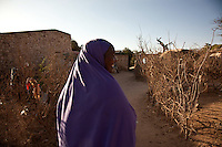 """Koos Aw Dahir - 40.Has been living in State House since 1992 .11 children - oldest, 22, youngest, 3.Koos looks after four of Siida's ( a new arrival from Mogadishu)  children...""""I have 11 children and my own problems, but I was touched by the problems of Siida.  I fled Somaliland during the 1988 war in Somalia so I know the problems of a refugee.  I cannot forget the war.  There was fighting, bullets.  Our men were being slaughtered in front of us like goats.  When we fled, we were afraid of wild animals.  Hyenas are around during war - they like the taste of human flesh.""""  ..""""When people first arrive, they are very afraid. They still have the feeling of where they've come from.  When I look at them, it's like looking at people running out of a burning house.  The new families who come here have nothing so they rely on us.""""  .. """"When it was built, State House was very beautiful.  I never went in and saw it, the closest you could get was the gate.  But people who'd seen inside used to tell stories, it was marvelous.  .There are so many problems here now though.  There is no water, no medical centre, no playgrounds for the children."""".  .""""I want the international community to look with a kind eye on the community living in State House.  Already we are displaced in our own country with no water, education, health services.  At the same time, we have another group of refugees adding to our problems.""""."""