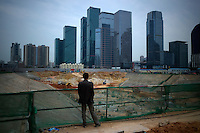 A man look at a construction site and new skyscrapers near the Civic Center of Shenzhen, China on Feb. 7 2012.
