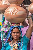 Abhaneri, Rajasthan, India.  Hindu Rajasthani Woman Steadies Pots on her Head as she Prepares to walk.
