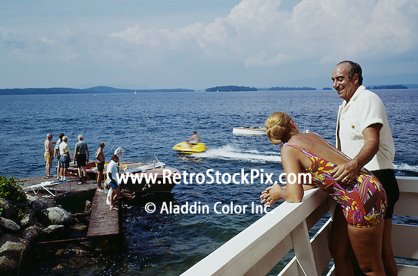 Belknap Point, Gilford, NH. Couple watching boaters from their balcony