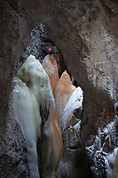Three climbers stand on top of an iron stained ice pillar about 100m below the ground level, Sweden
