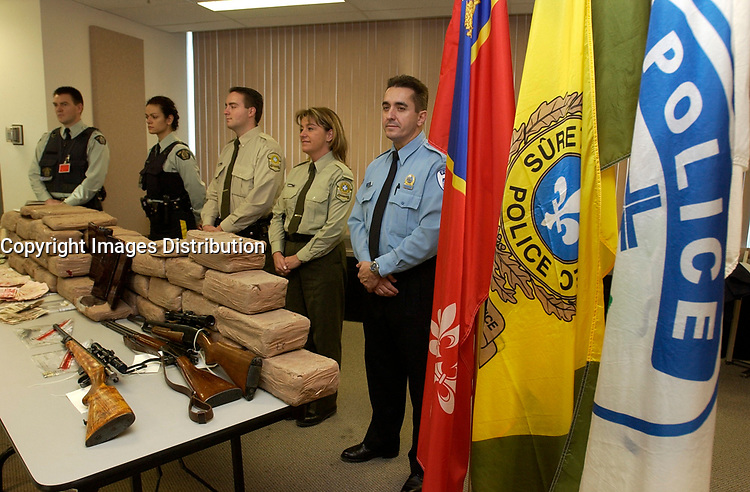 December 04,  2002, Montreal, Quebec, Canada; <br /> <br /> Quebec Provincial (Surete du Quebec) and Montreal City (SPCUM) Policemen show drug, guns and money<br /> seized during a recent drug bust,to the medias,<br />  December 04, 2002 in Montreal, Canada.<br /> <br /> 15 people presumably involveld in a 2 billion Can $ drug deal, where arrested after a joint operation by the RCMP, Quebec Province and Montreal City Police.<br /> <br /> <br /> <br /> (Mandatory Credit: Photo by Sevy - Images Distribution (©) Copyright 2002 by Sevy<br /> <br /> NOTE :  D-1 H original JPEG, saved as Adobe 1998 RGB.<br />  Uncompressed and uncropped original  size file available on request.