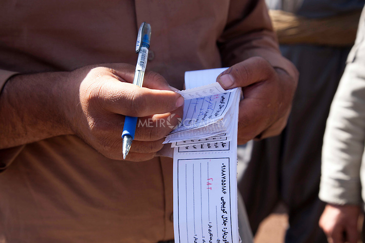 SHABADEEN, IRAQ: Khesraw writes receipts for the smugglers .to take across the border. The receipts ensure that the smugglers are paid once they reach the other side...Thousands of Kurdish smugglers make a living ferrying goods between Iraq and Iran. They smuggle everything from clothes, to make-up, to alcohol which is forbidden in Iran. The smugglers make around 100,000 Iranian Rials ($8 USD) per journey and make 3 journeys per day...Photo by Aram Karim