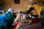 2011 - Juba, Republic of South Sudan - Lushi Rashid (C), a 29 year old muslim South Sudanese woman, gives birth to her fifth child at her family home with the help of her aunt (R) and Regabia Ahmad (L), a qualified birth attendant, in Juba, the capital city of South Sudan. Regabia has been delivering babies in South Sudan for over twenty years. she was trained by the health ministry and works at a local primary health clinic. With fewer than 100 trained midwives for a population of over eight million, South Sudan has the highest maternal mortality rate in the world.  One in seven South Sudanese women is likely to die because of complications from delivery. Just 10 per cent of South Sudanese women have access to medical professionals during childbirth. Photo credit: Benedicte Desrus