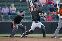 Kannapolis Intimidators catcher Seby Zavala (21) makes a throw to second base as home plate umpire Tom West looks on during the game against the Augusta GreenJackets at Intimidators Stadium on May 30, 2016 in Kannapolis, North Carolina.  The GreenJackets defeated the Intimidators 5-3.  (Brian Westerholt/Four Seam Images)