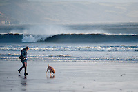 Friday 03 January 2014<br /> Pictured: A woman walks her dog along Saundersfoot Beach,West Wales with the waves crashing in the background<br /> Re: Storm force winds and some of the highest tides in decades hit Wales early on Friday.