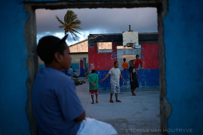 Children play basketball in a partially destroyed building on Ebeye, Marshall Islands on June 21, 2012. Ebeye island is packed with children, and the median age is around 18 years old. Classroom capacity in public schools in not sufficient, while many families can not afford the private schools run by Christian missionaries on the island, leaving hundreds of children out of school each year.