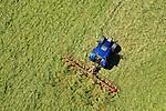 Foto: VidiPhoto<br /> <br /> HOMOET – Melkveehouder Nico Dirksen uit Elst (Gld) schudt maandagmiddag het pasgemaaide gras van een weiland voor het vluchtheuvelkerkje (1869) in het buurtschap Homoet. Het grasland is eigendom van de Hervormde gemeente Valburg-Homoet en wordt verpacht aan Derksen. Voor de Betuwse melkveehouder is dit de eerste snede van het jaar, net als bij de duizenden andere boeren die op dit moment hun gras binnen halen. Door het natte en koude voorjaar is de eerste grasoogst een maand later dan gebruikelijk. Bovendien is het gras grof en de kwaliteit flink lager. Minder voedingswaarde is echter ook minder melkopbrengst. Dat betekent dat het ingekuilde gras komende winter verrijkt moet worden met extra krachtvoer. Omdat ook de grasmat flink geleden heeft door kou en vocht, worden er dit jaar niet meer dan drie snijrondes verwacht, waar vier gebruikelijk is. Dat betekent dat ditmaal niet door de droogte, maar door juist teveel water vermoedelijk een tekort aan wintervoorraad ontstaat. Ieder nadeel heeft echter ook z'n voordeel. Door de regen en kou is er een eind gekomen aan de muizendplaag. Twee jaar geleden werd bij Dirksen al het gras door de knaagdieren opgevreten. De veeboer bezit 50 melkkoeien en 50 stuks jongvee.