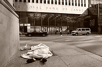 A homeless woman sleeping on the sidewalk facing  the Royal Bank of Canada building on King Street West in downtown Toronto, April 20, 2007.<br /> <br />     photo by Pierre Roussel - Images Distribution