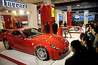 Visitors look at a Ferrari 599 GTB Fiorano, the first time its been seen in China at the 2006 International Automotive Exhibition in Beijing..25 Nov 2006
