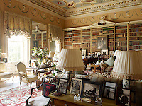 The 18th century library has a hand-painted ceiling and walls of shelves housing a collection of antique leather books