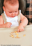 10 month old baby girl sitting in high chair eating round cereal using pincer grip Caucasian vertical