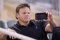 Former minor league baseball player and manager Torre Tyson watches the Major League Baseball Home Run Derby on his smart phone between innings of the South Atlantic League game between the Hagerstown Suns and the Kannapolis Intimidators at Kannapolis Intimidators Stadium on July 10, 2017 in Kannapolis, North Carolina.  The Suns defeated the Intimidators 8-5.  (Brian Westerholt/Four Seam Images)