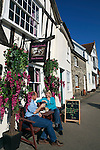 United Kingdom, England, Suffolk, Lavenham: Couple sitting outside the Tickled Pink Tea Rooms