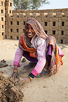 Rajasthan, India.  Woman Preparing Mud for Husband to Put into Brick Molds.  Note the toe rings and ankle bracelets.