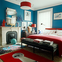 """A Fornasetti-inspired rug is one of the bright red accents in the master bedroom which is painted a deep """"Caribbean"""" blue; the bench at the end of the bed is an Anthony Todd design"""
