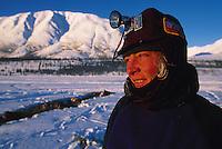 Portrait of an Iditarod musher in hat and headlamp. Alaska.