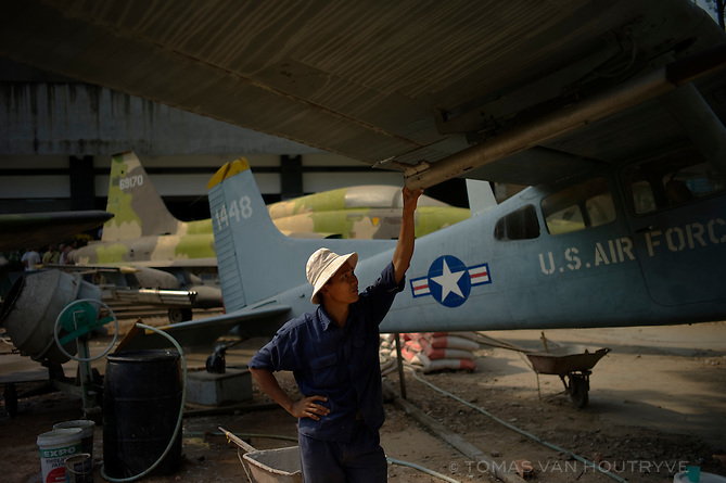 A man reaches to touch the wing of a captured US military airplane at the Vietnam War Remnants Museum in Ho Chi Minh City (Saigon), Vietnam on 8 March 2010.