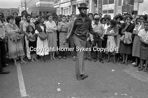 Notting Hill London during the annual Carnival. Group of teenagers stand in circle to watch a man dancing alone. 1980s UK