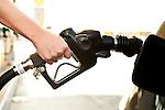 USA, California, Lawndale, Female hand inserting fuel pump into car gas tank