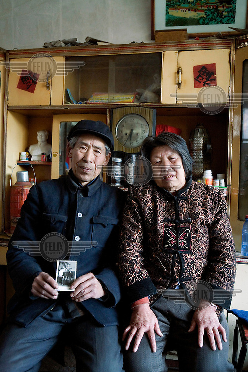 Yang Wan Ying and his wife Yang Shu Xia hold up a photograph of their son, Yang Shi Liang. Their son has been in jail for over a decade waiting for his death sentence to be carried out following a confession that he made while under torture. The couple believe that the court proceedings and evidence surrounding the case to be suspect and have been petitioning for an investigation into their son's conviction.