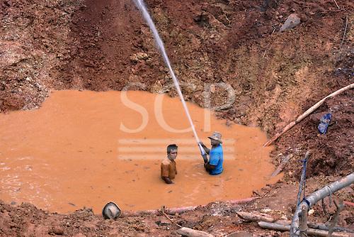 Maria Bonita, Xingu, Brazil. Garimpo illegal gold mine with garimpeiros in muddy water using high pressure hose.