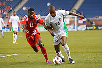 Guadeloupe midfielder Gregory Gendrey (14) dribbles the ball  past Panama midfielder Armando Cooper (11) during the CONCACAF soccer match between Panama and Guadeloupe at Ford Field Detroit, Michigan.