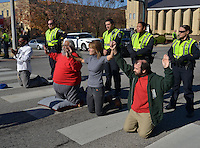 STAFF PHOTO BEN GOFF  @NWABenGoff -- 11/25/14 Fayetteville police officers prepare to arrest demonstrators Jared Carter, from left, David Garcia, Jane Stitt and Nik (CQ) Robbins during a protest organized by the OMNI Center for Peace, Justice & Ecology in front of the Washington County Courthouse in Fayetteville on Tuesday Nov. 25, 2014. The four volunteered to be arrested for obstructing traffic. The demonstration was in response to the decision Monday night by the St. Louis County grand jury not to indict police officer Darren Wilson, who fatally shot Michael Brown in Ferguson, Mo.